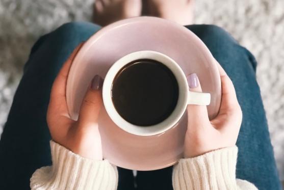 コーヒーカップを持つ人の手